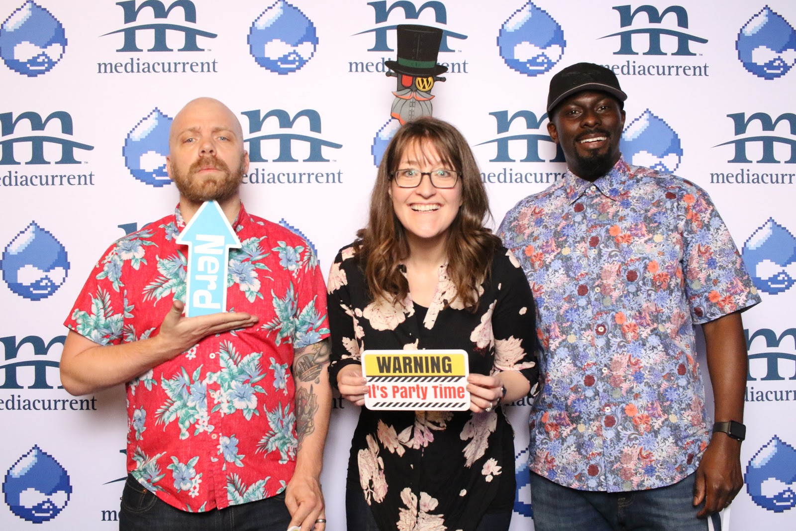 3 Mediacurrent employees posing in with props in a photobooth