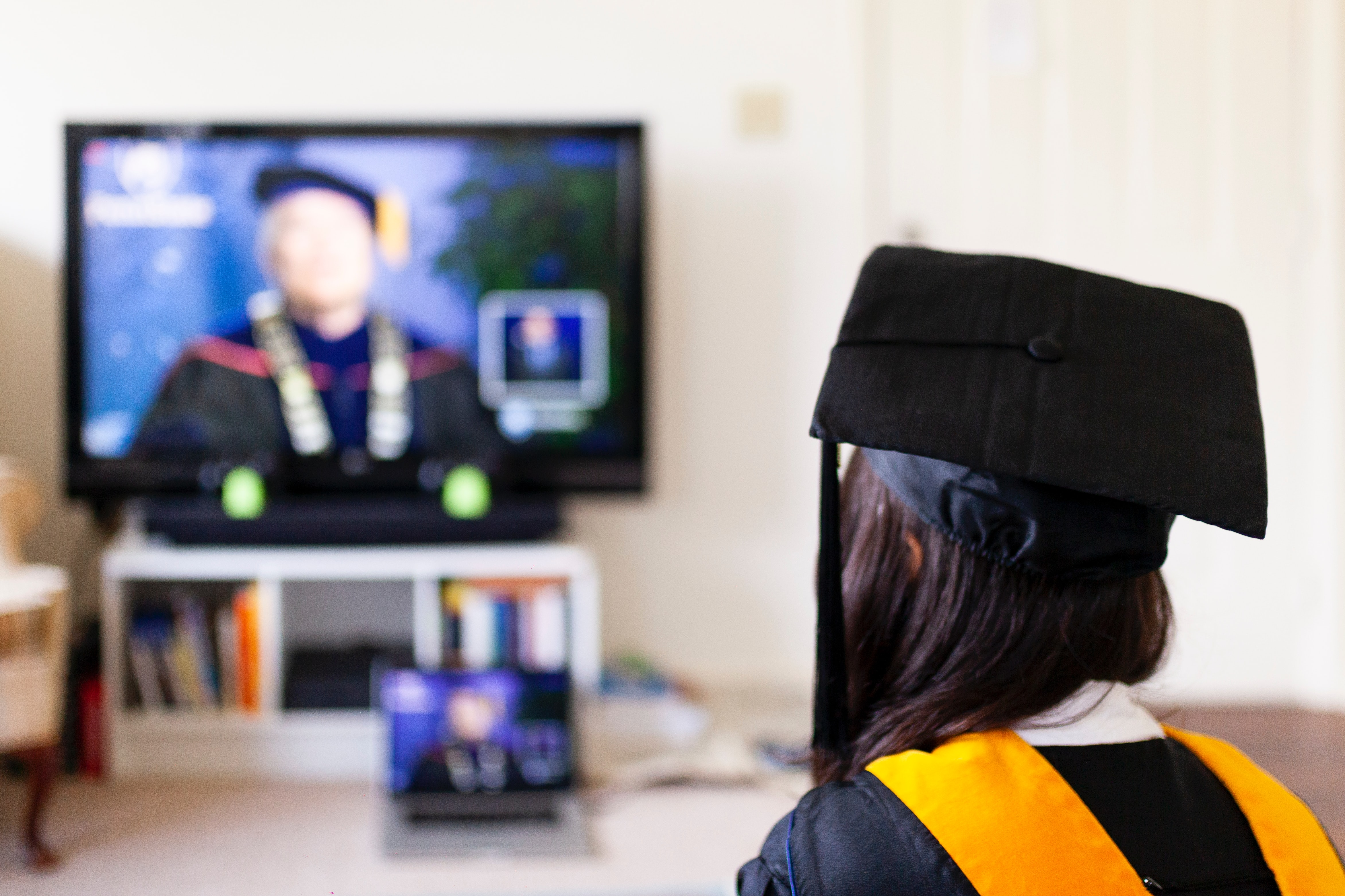 student in cap and gown attending a virtual college graduation ceremony