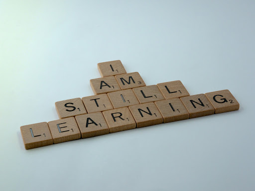 "Photo of scrabble letters spelling ""I AM STILL LEARNING"""